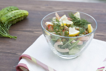 Salad of cooked squid, fresh vegetables and herbs in glass bowl
