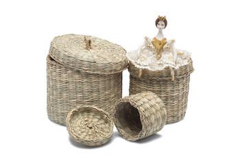 Doll sitting on wicker baskets