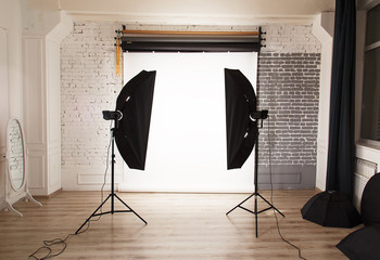 Empty photo studio interior with white background and lighting e