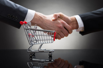 Businesspeople Shaking Hands With Mini Shopping Cart