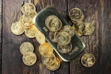 schweizer Goldvreneli mit Goldbarren auf rustikalem Holzhintergrund