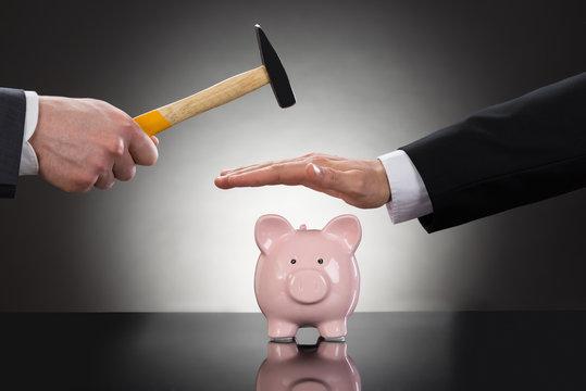 Businessman Saving Piggybank From Hammering