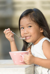 Cute little asian girl eating cereals in morning.