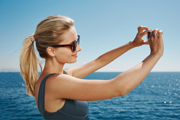 Happy fitness selfie blonde girl smiling and taking self portrai