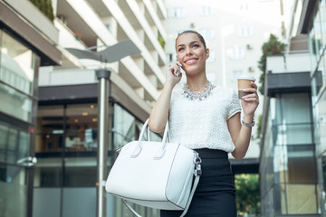 Young businesswoman holding coffee to go and talking on the phon