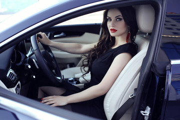 gorgeous woman in elegant dress posing in luxurious auto