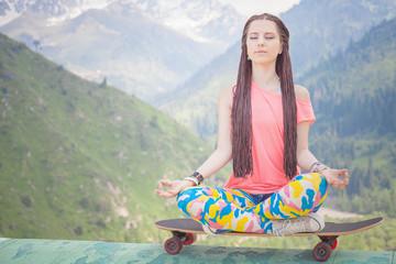 hippie fashion girl doing yoga, relaxing on skateboard at mountain