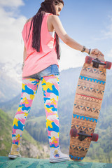 Hippie young and beautiful girl with longboard skateboard at mountain