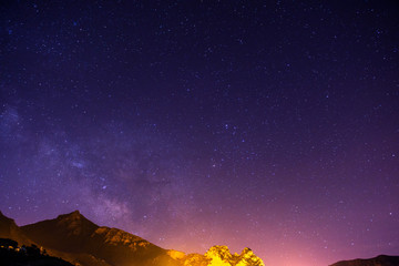 The starry sky above rocky mountains.