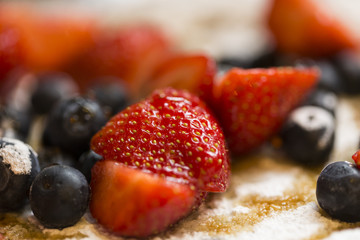 Strawberries and blueberries close up on a pancake with syrup