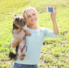 Happy woman and yorkshire terrier dog having fun takes selfie po