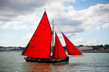 Traditional wooden boats with read sail.