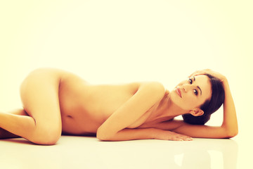 Naked woman lying against the floor