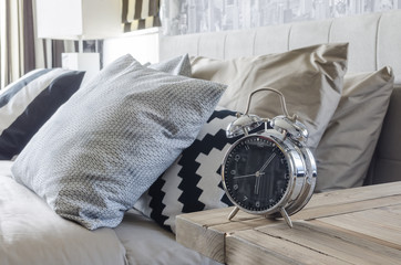 classic style alarm clock on wooden table in bedroom