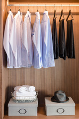 shirts and pants hanging  on rack in wooden wardrobe