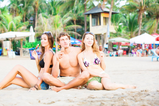 Group of happy young people eating ice cream on the beach