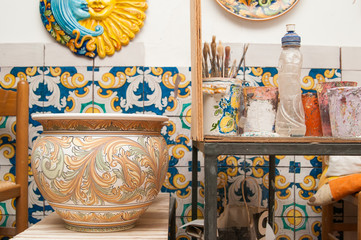 Decorated ceramic vase in the workshop of a decorator of Caltagirone and a worktable with tools