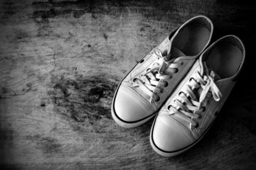 White canvas shoes on old wooden floor