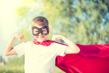 Little boy wearing superhero costume showing muscles