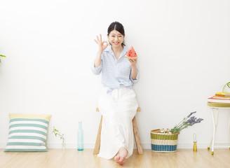 部屋で西瓜を食べる女性 OKサイン