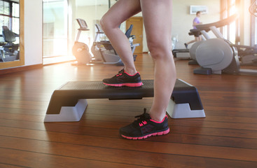 Young woman doing step aerobics while in health club