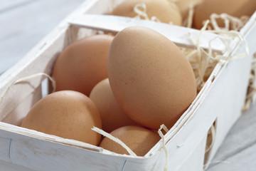 Eier im Bastkörbchen auf Holztisch, Nahaufnahme