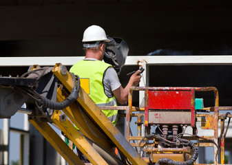 Worker wlding metal beams