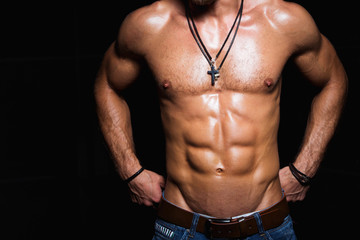 Muscular and sexy torso of young sporty man in jeans with
