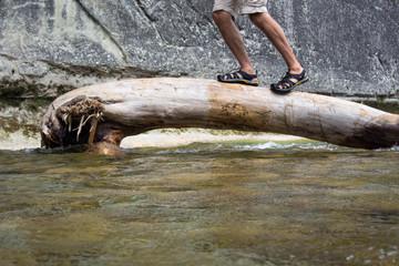 Person balanciert über einen Holzstamm über einem Bach