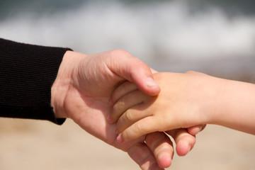 Frau hält reicht einem Kind die Hand