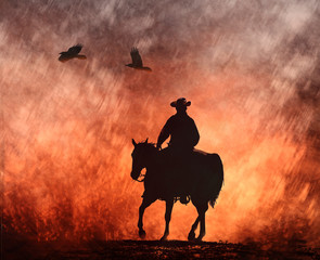 A cowboy on a horse riding into red fire with crows flying above.