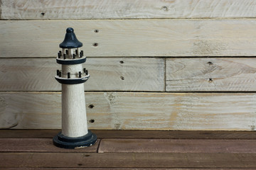 Lighthouse against a wood background