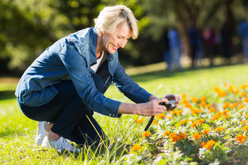 senior woman taking photographs of flowers