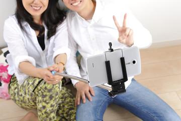 室内で自撮り棒で撮影している男女カップル