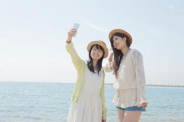 海辺で記念撮影をする女の子たち