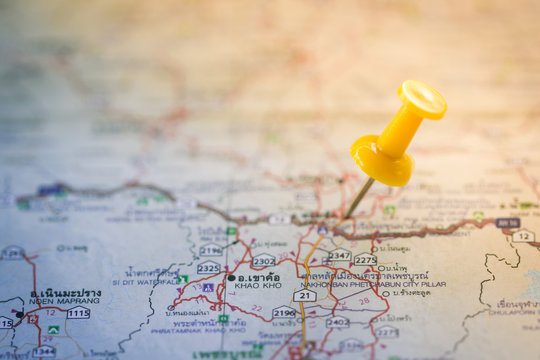 Travel concept with yellow pushpin on map,color filter effect