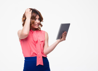 Worried woman using tablet computer