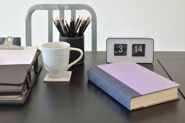 work table with book,pencils, cup of coffe and clock in a home
