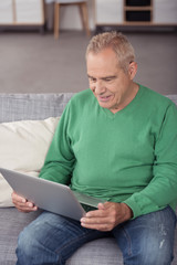 älterer mann schaut auf seinen laptop