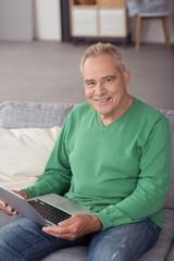 moderner senior mit seinem notebook auf dem sofa