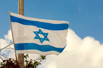 White and blue flag of Israel over the clouds in sky