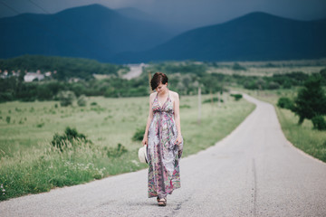 Beautiful hippie woman posing on a green field with mountains and dark clouds on the background.