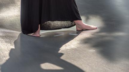 nackte Füße in schwarzem Kleid auf glänzender Fläche
