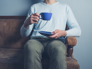 Man on sofa drinking coffee