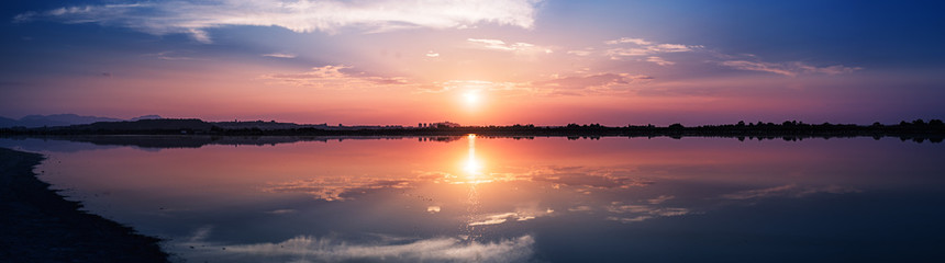 Perfectly specular reflection on the pond at sunset - panoramic view