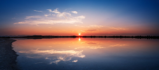 Perfectly specular reflection on the water at sunset - panoramic view