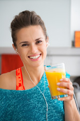 Smiling fit woman holding fresh juice in a glass