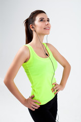 Young beautiful sporty girl listens to music