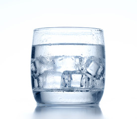 Glass of cold water and ice on background