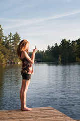 girl using her phone to take a picture of a sunset over a lake